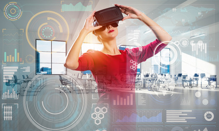 Young and modern business woman in red dress using virtual reality headset while standing inside office building with digital media interface.