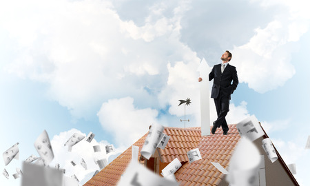 Conceptual image of young businessman in suit looking upside and holding big white arrow in hand while standing on brick roof among flying papers and cloudy skyscape view on background. Stock Photo