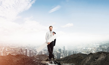 Confident and young businessman in suit holding huge white arrow which pointing away as symbol of development and improvement. Cityscape view and cloudy sky on background 스톡 콘텐츠