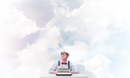 Young man writer in hat and eyeglasses using typing machine while sitting at the table with cloudy skyscape on background. Stock Photo