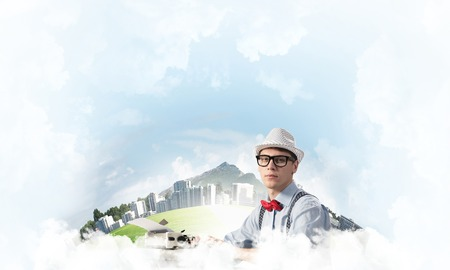 Young man writer in hat and eyeglasses using typing machine while sitting at the table with floating city and cloudy skyscape on background.