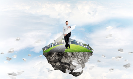 Conceptual image of young confident businessman in suit with big white arrow in his hand standing among paper planes on the flying island with cloudy skyscape view on background.