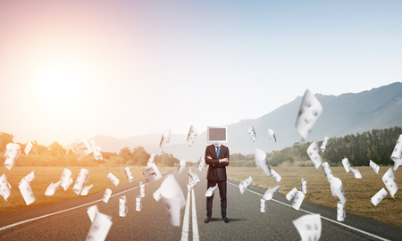 Businessman in suit with monitor standing on the road among flying papers with beautiful landscape