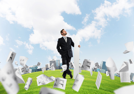 Young businessman in suit looking upside and holding big white arrow in hand while standing among flying papers on green meadow and cityscape view on background. Stock Photo