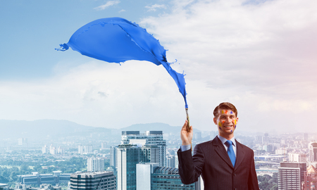 Successful businessman in black suit gesturing and smiling while standing with blue coloured splash against cityscape view on background. 스톡 콘텐츠