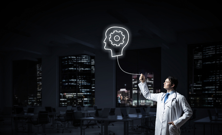 Conceptual image of confident doctor in white uniform interracting with glowing gear brain symbol while standing against night cityscape view on background. Stock Photo