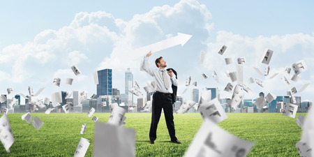Young and confident businessman in suit starting launching huge white arrow to the air Stockfoto