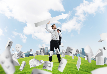 Young and confident businessman in suit starting launching huge white arrow to the air while standing among flying papers on green lawn and cityscape view on background. Stock Photo