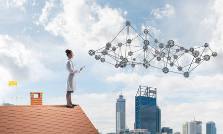 Young medical industry employee in white uniform standing at the top of building and interracting with social media network structure. Doctor on the roof. Cloudy skyscape on background
