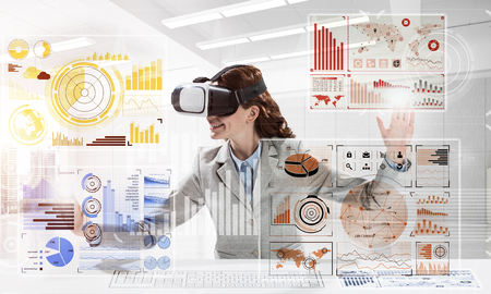 Portrait of confident and successful business woman in suit sitting inside office building with digital media interface and using virtual reality headset Stock Photo - 106911513