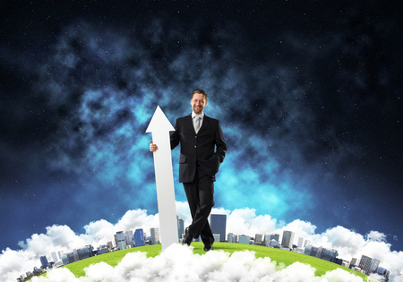 Successful businessman in suit pointing upside with huge white arrow in his hands while standing on Earth globe and dark space view on background. Elements of this image are furnished by NASA