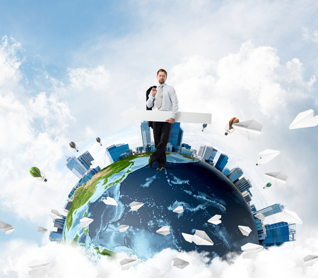 Ambitious and young businessman in suit pointing aside by means of big white arrow in hands while standing on Earth globe with sky view on background. Elements of this image are furnished by NASA Banco de Imagens