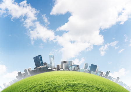 Panoramic view of modern cityscape with buildings and skyscrapers, meadow with green grass and blue cloudy sky on background. Wallpaper, backdrop with copyspace.