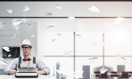 Young man writer in hat and eyeglasses using typing machine while sitting at the table indoors among flying paper planes and with office view on background. Foto de archivo