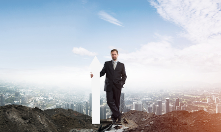 Horizontal shot of confident business man holding white arrow while standing among ruins with cityscape view on background.