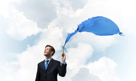 Horizontal shot of cheerful and young businessman in black suit standing with blue coloured splash against cloudy skyscape on background.