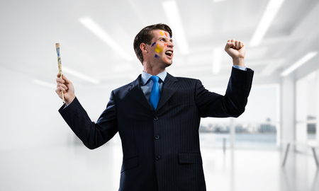 Horizontal shot of cheerful and young businessman in black suit gesturing and smiling while standing inside bright modern office.
