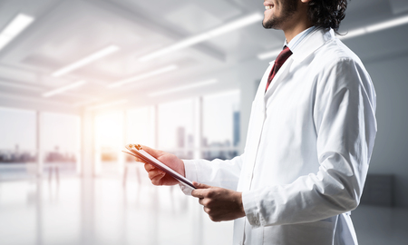 Cropped image of confident doctor in white sterile coat standing inside white hospital office building with sunlight on background.