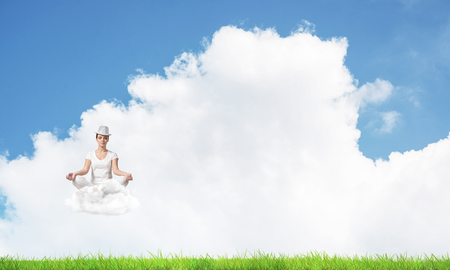 Young woman keeping eyes closed and looking concentrated while meditating on cloud in the air with bright and beautiful landscape on background.