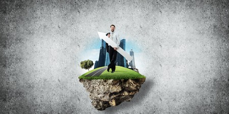 Conceptual image of young and confident business man in suit holding big white arrow in hands while standing on flying island against gray concrete background