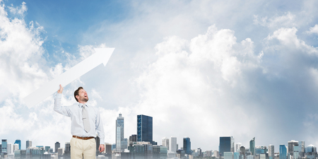Horizontal shot of young businessman throwing big white arrow in the air while standing against modern cityscape view and cloudy sky on background Banco de Imagens