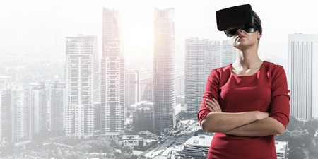 Conceptual image of young woman in red dress using virtual reality headset while standing outdoors with modern cityscape view on background Stock Photo