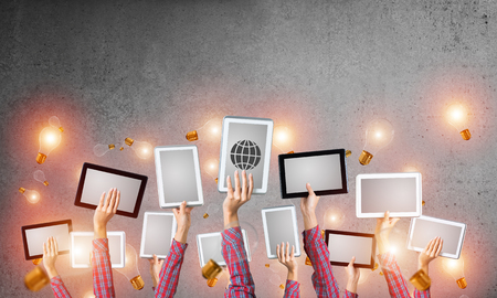 Set of tablets in female hands and glass bulbs fly around Stock Photo