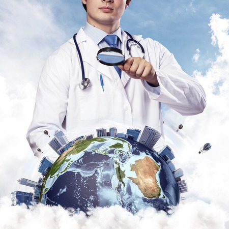 Cropped image of professional man doctor in white suit and stethoscope on neck discovering Earth globe through magnifier, with cloudy skyscape on background. Medical industry concept
