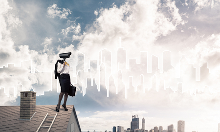 Faceless businesswoman with camera zoom instead of head standing on house roof Stock Photo