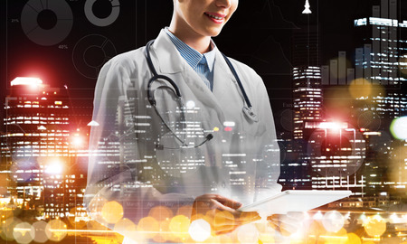 Cropped image of young medical industry employee standing outdoors and holding tablet in hands with night city view on background. Woman doctor using tablet. Double exposure with media interface