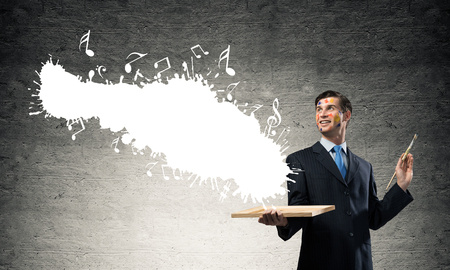 Horizontal shot of cheerful and young businessman in black suit gesturing and smiling while standing with white musical splash against dark wall on background. Stock Photo