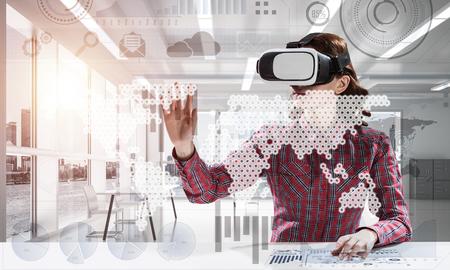 Moderne technologieën voor onderwijs door middel van jonge vrouwelijke student in geruit overhemd met behulp van virtual reality-bril en interageren met digitale media-interface.