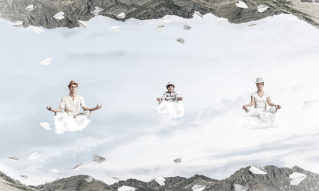 Young family keeping eyes closed and looking concentrated while meditating on clouds among flying paper planes and between two nature worlds.