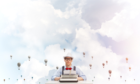Young man writer in hat and eyeglasses using typing machine while sitting at the table with flying aerostats cloudy skyscape on background. Stock Photo