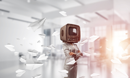 Cropped image of business woman in suit with old TV instead of head keeping arms crossed while standing among flying paper planes inside office building. Stock Photo