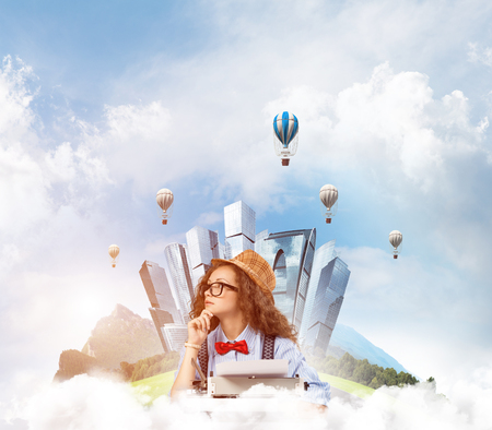 Young and beautiful woman writer in hat and eyeglasses using typing machine while sitting at the table with floating city island and cloudy skyscape with flying aerostats on background.