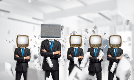 Businessmen in suits with old TV instead of their heads keeping arms crossed while standing in a row and one at the head with laptop inside office building. Stock Photo