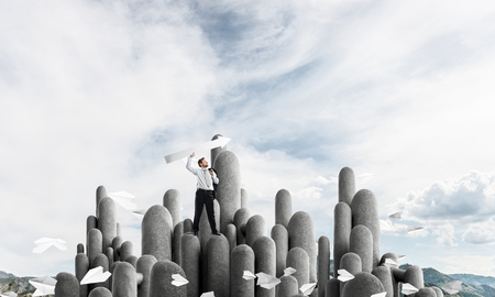 Horizontal shot of young and confident businessman in suit pointing away with white big arrow while standing on stone column with cloudy skyscape view on background. Stock Photo