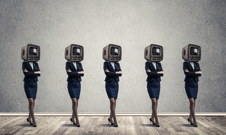 Business women in suits with old TV instead of their heads keeping arms crossed while standing in a row in empty room with gray wall on background. Stock Photo