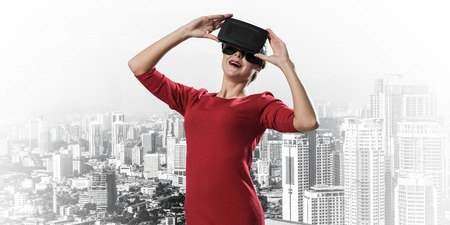 Horizontal shot of young and beautiful woman in red dress using virtual reality headset while standing outdoors with modern cityscape view on background