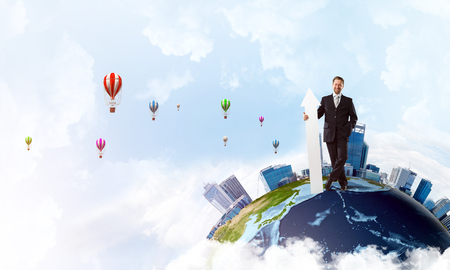 Young successful business man in suit pointing aside by means of big white banner in form of arrow while standing on Earth globe and flying balloons. Elements of this image are furnished by NASA
