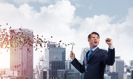 Horizontal shot of young and happy businessman in black suit holding paintbrush in his hand while standing against cityscape view and flying letters on background