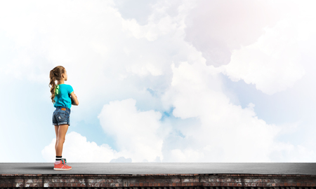 Cute kid girl standing on building roof with hands crossed on chest Banco de Imagens