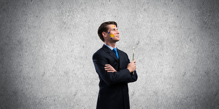 Conceptual image of confident and successful businessman in black suit standing against dark gray wall on background with paintbrush in hand