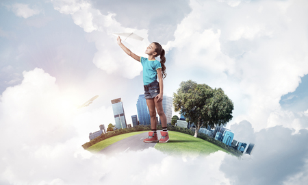 Cute kid girl on city floating island throwing paper plane Imagens - 108764863