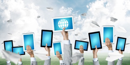 Set of tablets in male hands against nature background and paper planes in air