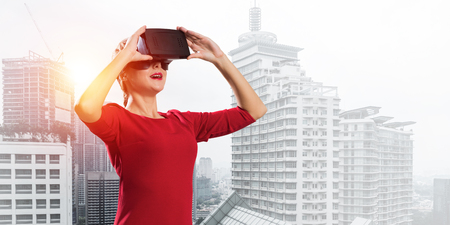 Beautiful and young woman in red dress using virtual reality headset while standing against cityscape view on background. Up to date technologies