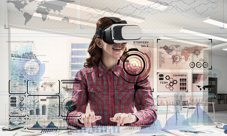 Horizontal shot of young and beautiful woman in checkered shirt using VR headset and media interface while sitting inside bright office building. Educational process with help of new technologies