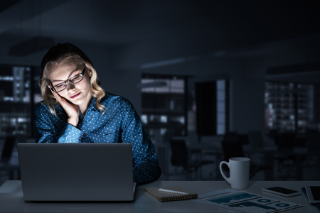 Young woman sitting in her room or office at late night. Mixed media Stock Photo