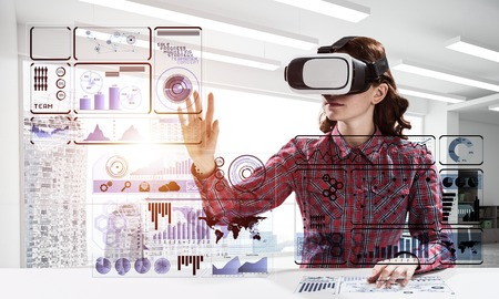 Young woman in checkered shirt using VR headset with digital media interface while sitting inside bright office building. Virtual reality technologies for education Stock Photo - 108881600